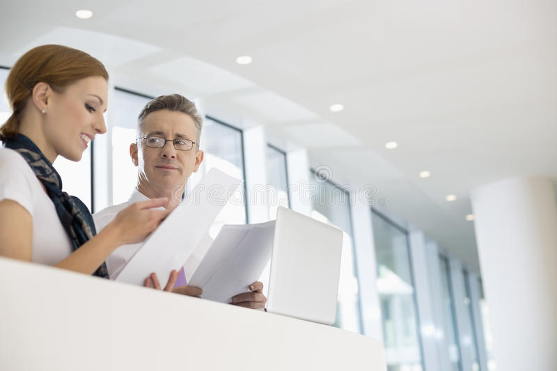 Business people discussing over documents in office stock photography