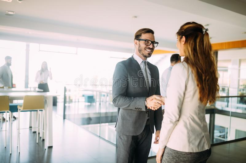 Business people discussing over documents in office lobby. royalty free stock photography