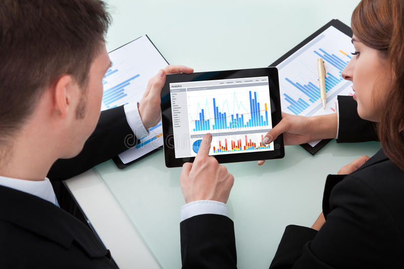 Business people discussing over graphs on digital tablet. Young business people discussing over graphs on digital tablet at office desk