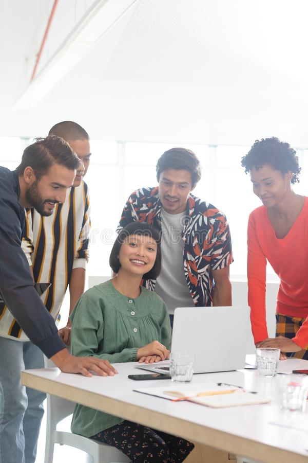 Business people discussing over laptop in the conference room. Front view of diverse business people discussing over laptop in the conference room at office royalty free stock photos