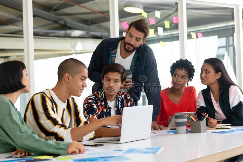 Business people discussing over laptop in the conference room. Front view of diverse business people discussing over laptop in the conference room at office royalty free stock image