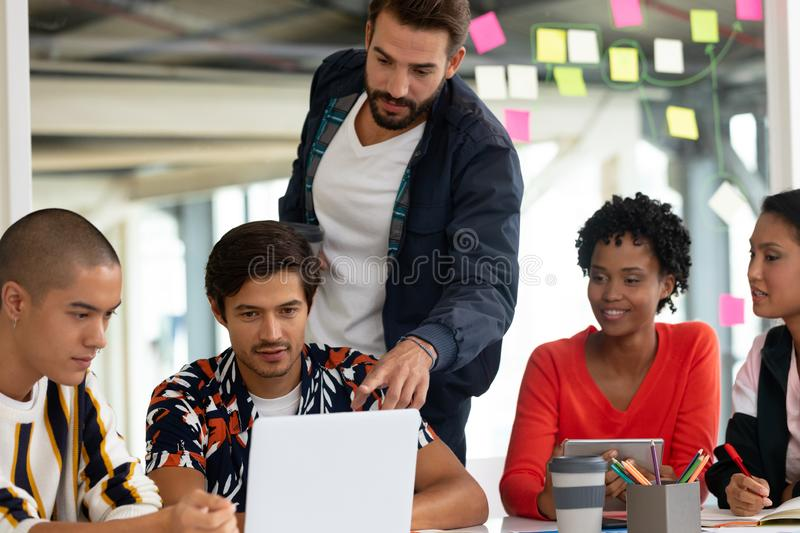 Business people discussing over laptop in the conference room. Front view of diverse business people discussing over laptop in the conference room at office royalty free stock images
