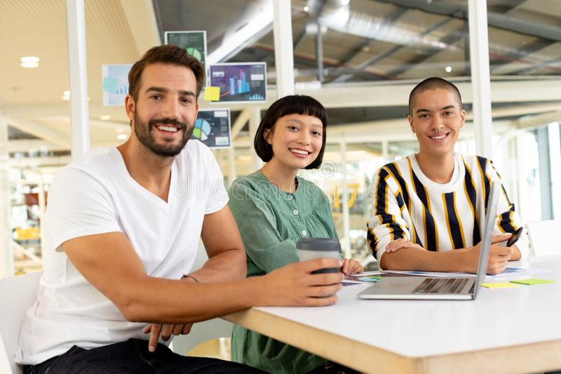 Business people discussing over laptop in the conference room. Front view of smiling diverse business people discussing over laptop in the conference room stock images