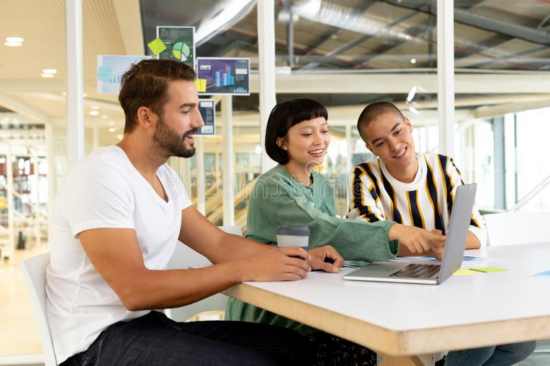Business people discussing over laptop in the conference room. Front view of smiling diverse business people discussing over laptop in the conference room at royalty free stock image