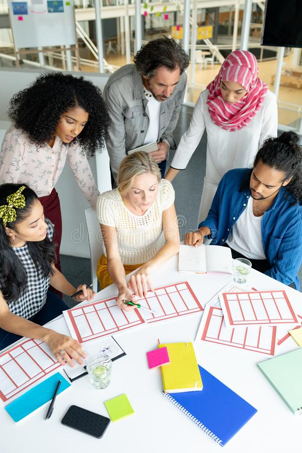 Business people discussing together over documents at conference room in a modern office. Front view of diverse business people discussing together over royalty free stock images