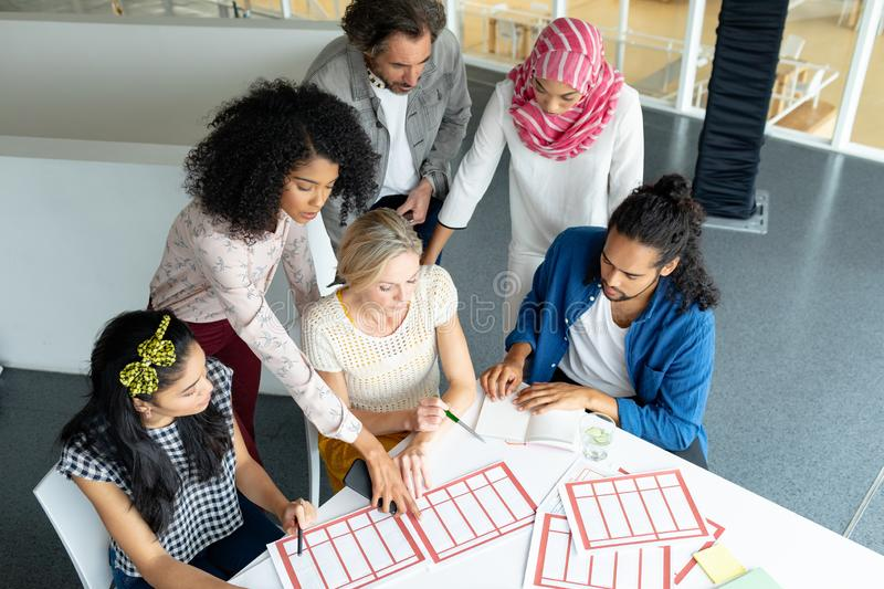 Business people discussing together over documents at conference room in a modern office. Front view of diverse business people discussing together over royalty free stock photos