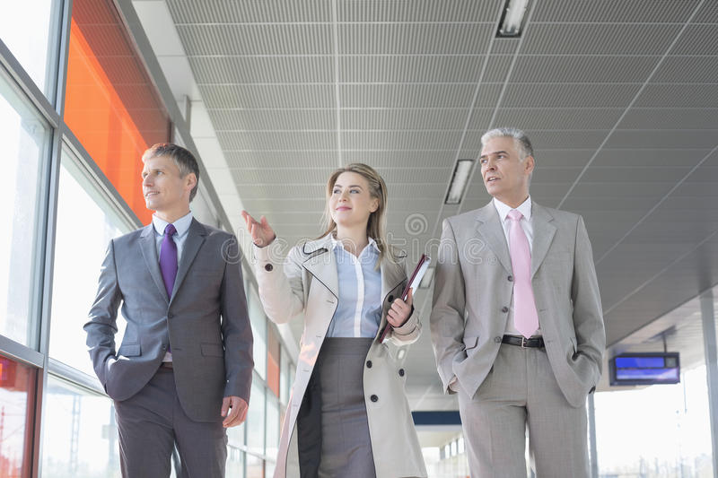 Business people discussing while walking on train platform stock photo