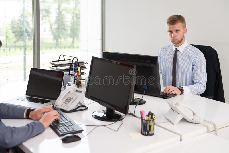 Business People Discussion At Computer. Happy Young Business Men Work In Modern Office On Computer stock photos