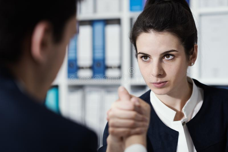 Business people doing arm wrestling. Competitive male and female business executives doing arm wrestling in the office and challenging each other royalty free stock photography