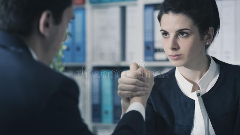 Business people doing arm wrestling. Competitive male and female business executives doing arm wrestling in the office and challenging each other stock photos