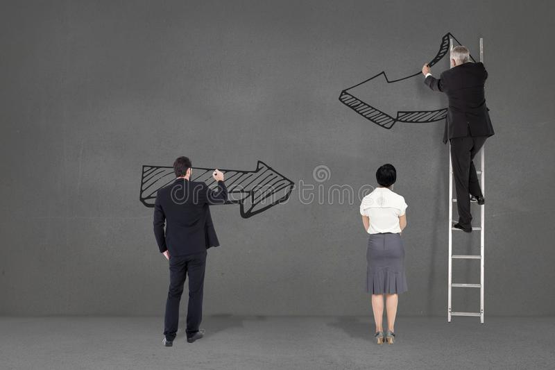 Business people drawing black arrows in a grey background stock illustration