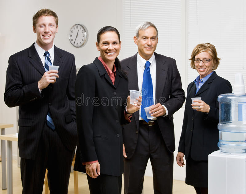 Business people drinking water at water cooler stock image