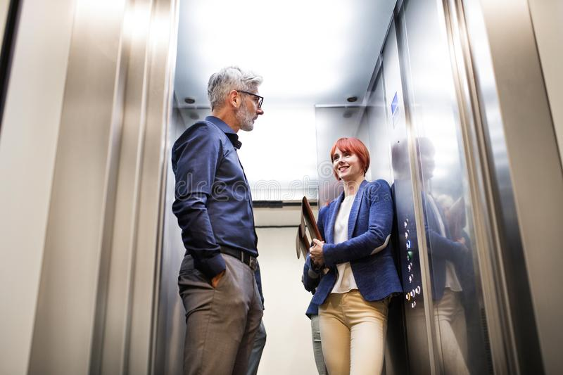 Business people in the elevator in modern office building. Two business people in the elevator in modern office building royalty free stock image