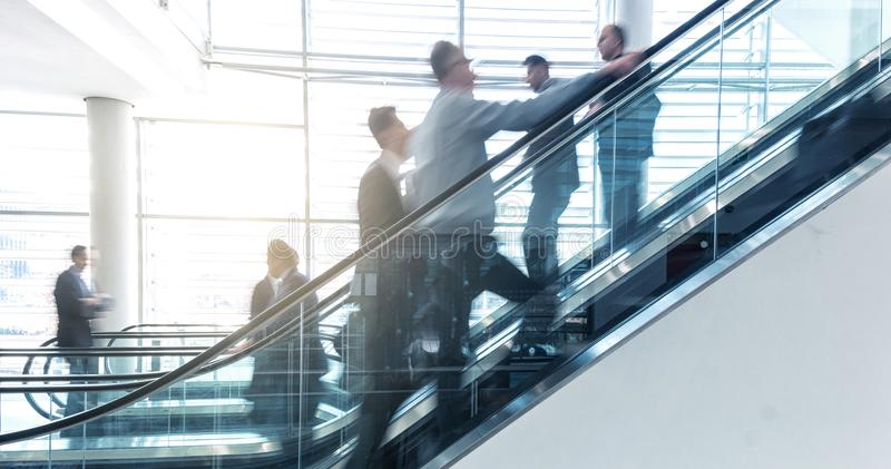 Business people on a escalator - business concept royalty free stock image