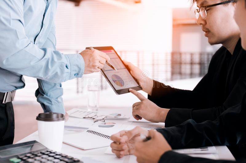 Business people examining financial reports and analyzing business growth in tablet screen. stock photo