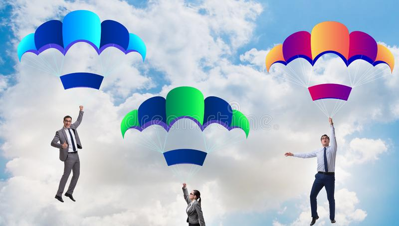 Business people falling down on parachutes royalty free stock photos
