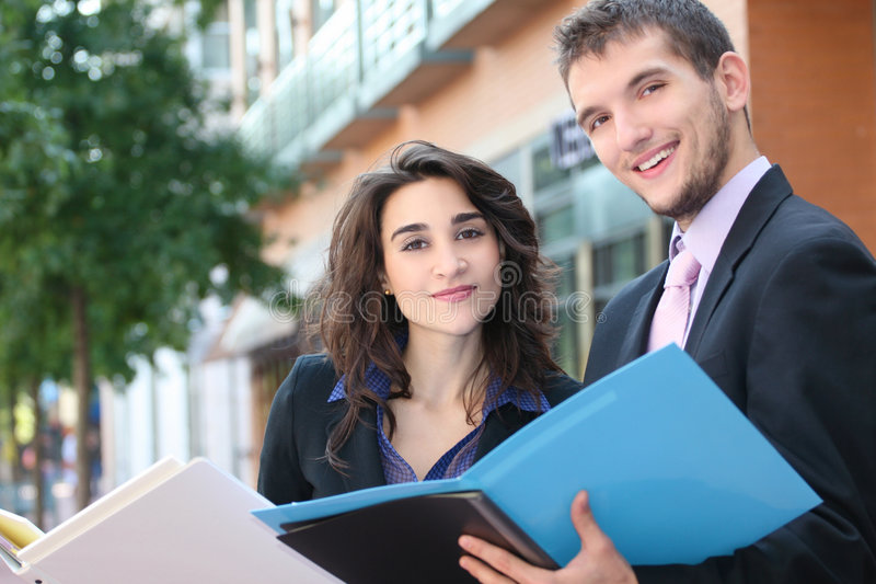 Business People with Folders. Two business people, young professionals, outdoors, at work - looking at folders. Suitable for a variety of political, economic royalty free stock image