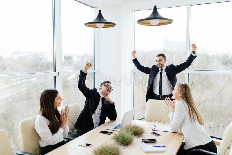 Business people in formalwear celebrate victory while sitting together at the table royalty free stock images