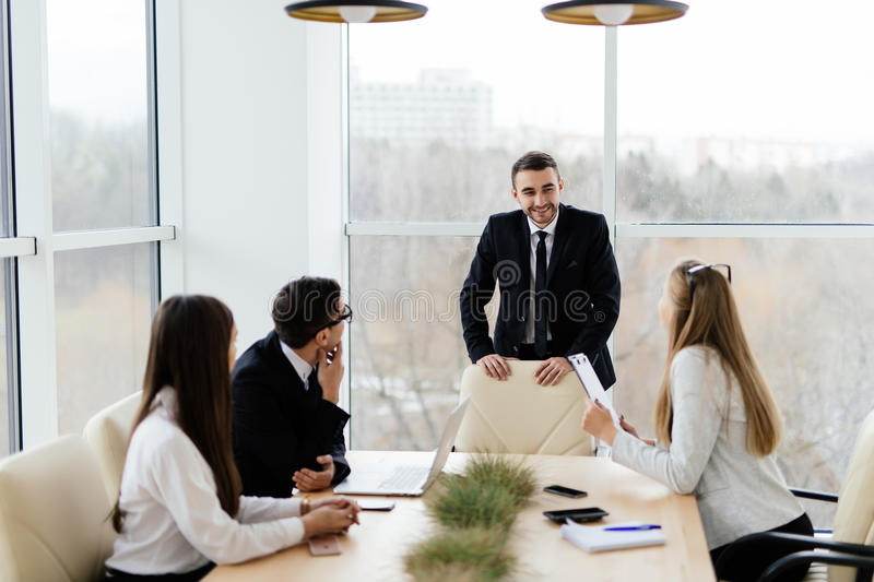 Business people in formalwear discussing with leader something while sitting together at the table royalty free stock images