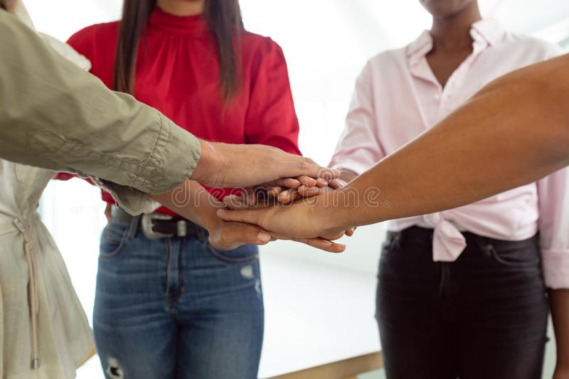 Business people forming hand stack in a modern office. Front view of team of diverse business people forming hand stack in a modern office royalty free stock photography