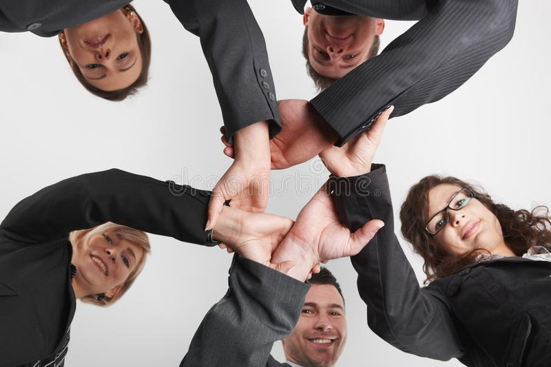 Business people forming ring of hands low angle. Happy caucasian business people wearing suit forming ring of hands low angle view, looking at camera. Isolated stock image