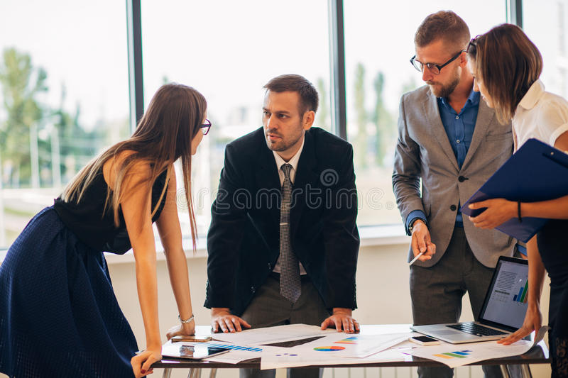 Business people gathered together at a table discussing an idea stock photos