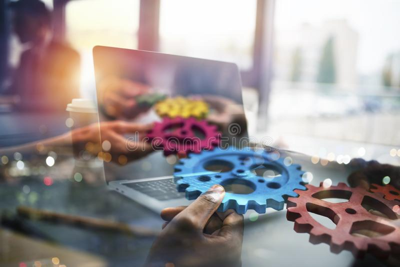Business people with gears in hand that exit from a laptop. concept of remote cooperation and teamwork. Double exposure royalty free stock photos
