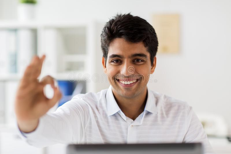 Businessman showing ok hand sign at office. Business, people and gesture concept - businessman with laptop computer showing ok hand sign and papers at office stock photography