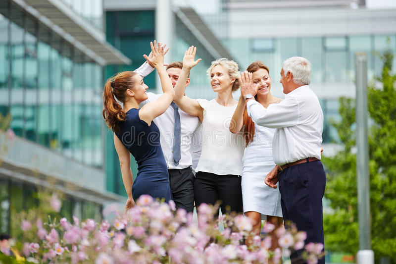 Business people giving high five stock images