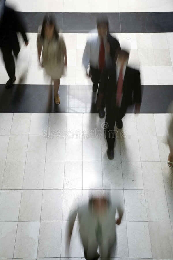 Business people going to work. Walking over a marble corridor