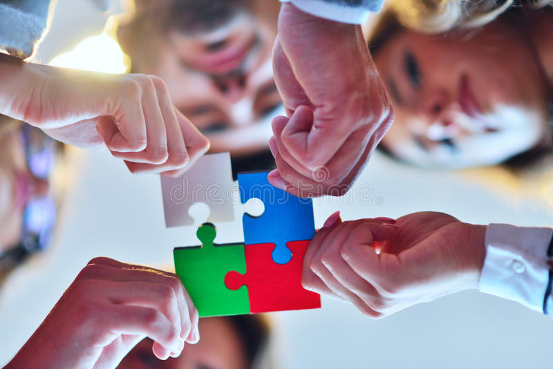 Business people group assembling jigsaw puzzle and represent team support. And help concept, top view perspective at modern bright office interior royalty free stock photos
