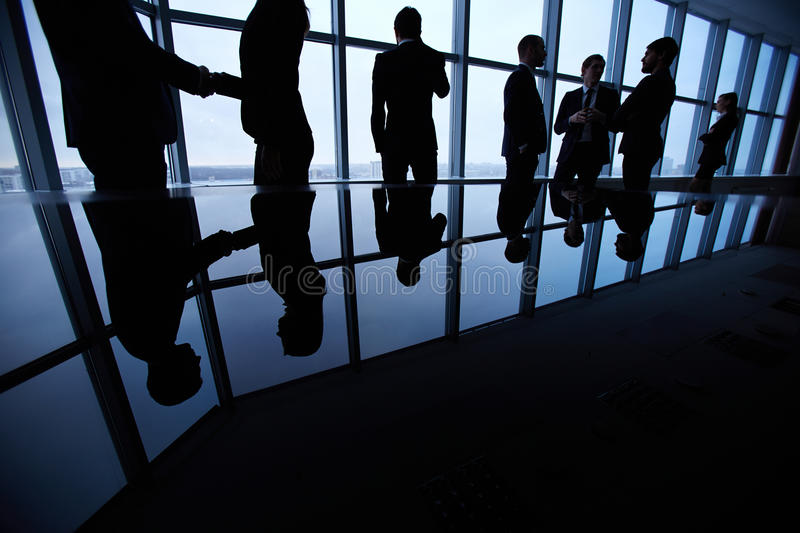Business people. Group of business people standing against office in board room and interacting stock photography