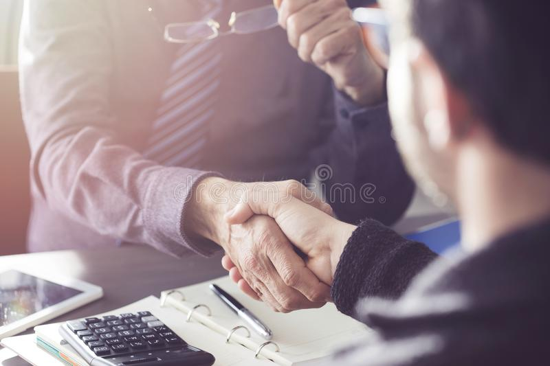 Business people hand shaking after a deal in office stock images