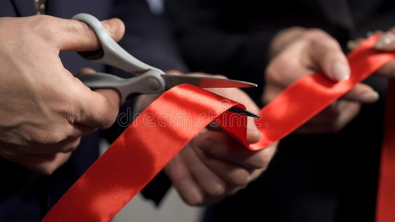 Business people hands cutting red ribbon close-up, new project, opening ceremony stock images
