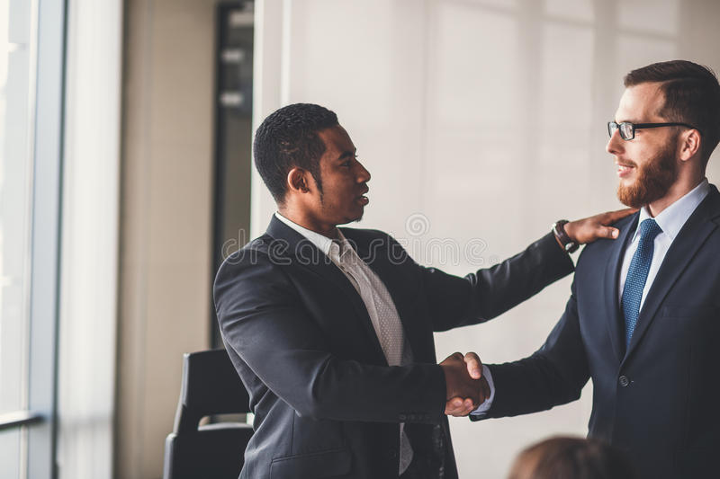 Business People Handshake Greeting Deal Concept. Business people shaking hands, finishing up a meeting stock image