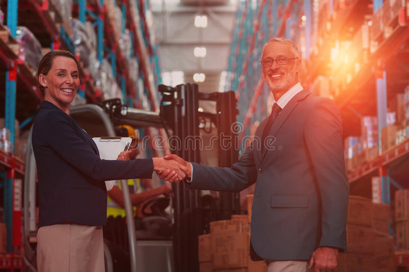 Business people are handshaking and looking the camera in front of workers stock photos