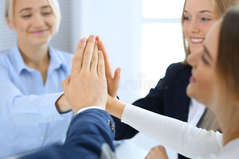 Business people happy showing teamwork and giving five showing unity and partnership. Success and friendship concepts stock images