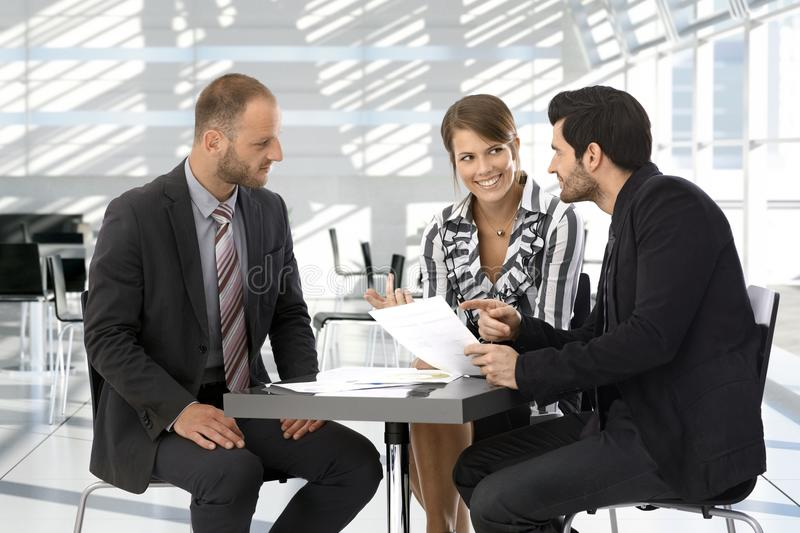 Business people having discussion by coffee table stock image
