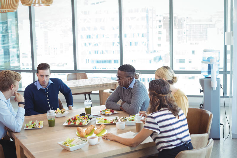 Business people having lunch at office cafeteria royalty free stock photography