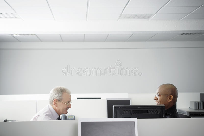 Business People Having Meeting In Office Cubicle. Multiethnic business people having casual meeting in office cubicle stock photos