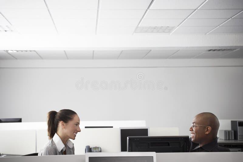 Business People Having Meeting In Office Cubicle. Multiethnic business people having casual meeting in office cubicle royalty free stock photo