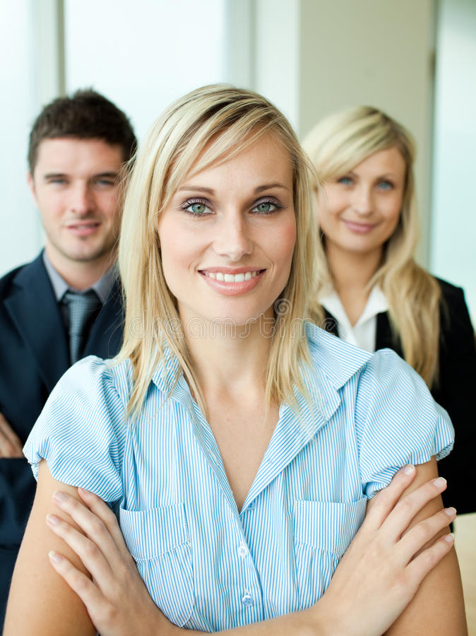 Business people headed by a woman with folded arms stock photo