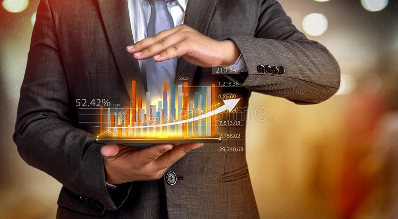 Business people hold a tablet, plan and strategy and display virtual holograms of statistics, financial graphs, securities and royalty free stock photo