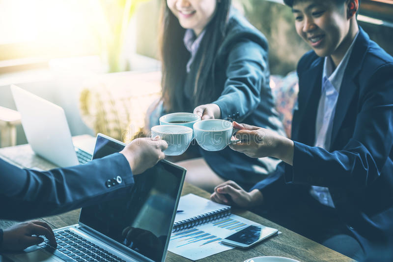 Business people holding cups of coffee while having coffee break royalty free stock image
