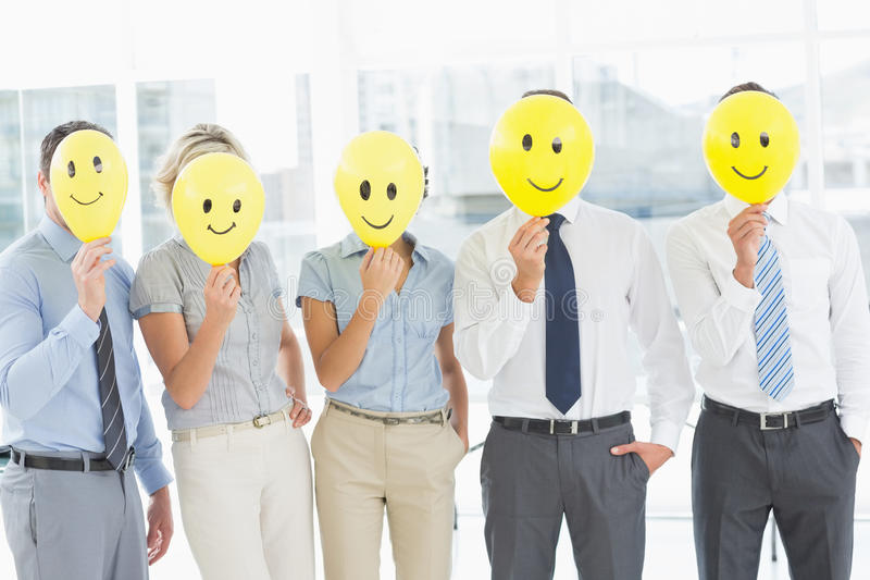 Business people holding happy smiles in front of faces stock images