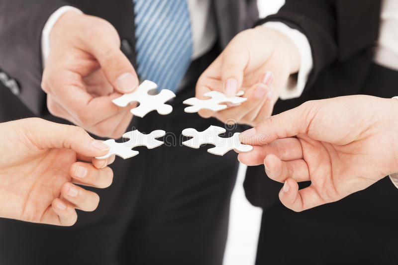 Business people Holding Jigsaw Puzzle. Teamwork concept stock image