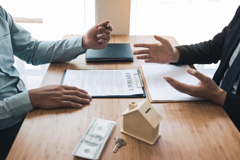 Business people home sales broker is using a pen pointing to the house model and describing the various components of the house stock photography