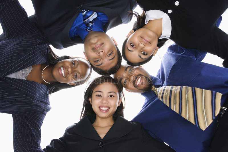 Business people in huddle. Low angle portrait of multi-ethnic business group of men and women in huddle looking at viewer