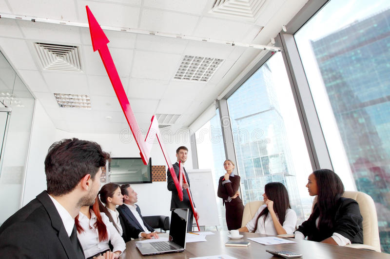 Business people and income growth. Business people discuss red arrow of income growth at meeting stock photography