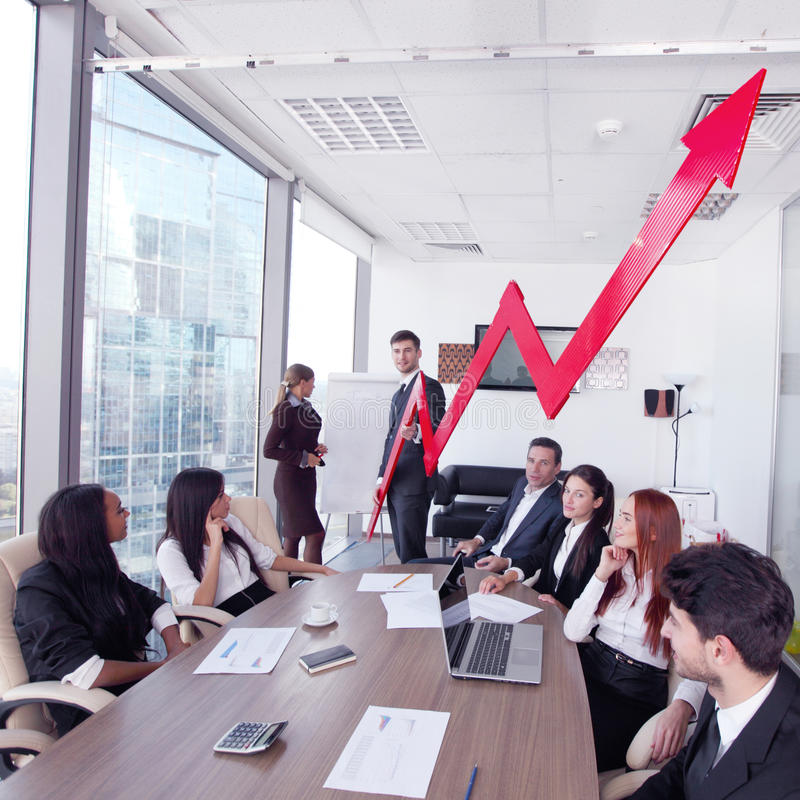 Business people and income growth. Business people discuss red arrow of income growth at meeting royalty free stock image